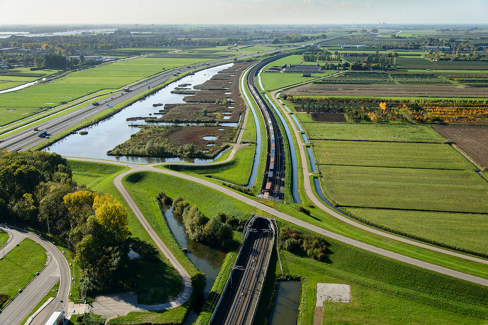 Nederland, Gelderland, Betuwe, 24-10-2013; Betuweroute, ter hoogte van Echteld. De goederenspoorlijn loopt parallel aan autosnelweg A15. De goederentrein is onderweg naar de haven van Rotterdam. Rechts boomkwekerijen tussen de weilanden.<br /> Betuweroute, railway from Rotterdam to Germany, near Echteld. The freight railway runs parallel to highway A15. The freight is on its way to the port of Rotterdam.luchtfoto (toeslag op standaard tarieven);<br /> aerial photo (additional fee required);<br /> copyright foto/photo Siebe Swart.