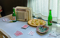 This is a re-creation of a typical 1950s kitchen, including period radio, playing cards, ash tray and soda bottles.