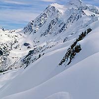 A snowboarder carves powder below Mount Shuksan, near Mount Baker Ski Area.