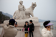 """Visitors getting photographed at the monument in Hoedong (Jindo island) which is showing praying grandmother """"Old Lady Pong"""" and a tiger related to the Jindo myth. Jindo is the 3rd biggest island in South Korea located in the South-West end of the country and famous for the """"Mysterious Sea Route"""" or """"Moses Miracle"""" which is happening during full moon in spring."""