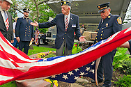 Merrick, New York, USA. September 11, 2011. Removing American Flag to reveal monument made with steel from World Trade Center, at the Merrick Post #1282 American Legion Tenth Anniversary of 9/11 event are (left to right) Rabbi Paul Kirchner, Father Eric Fasano, Adjutant Robert Tom Riordan PCC; and North Merrick Fire Dept. Ex. Chief Henry Hinrichs, at Merrick Veterans Memorial Park.