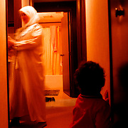 A young boy watches his mother pass from the women's prayer area into the kitchen during the end of the 1999 Ramadan holiday at the Muslim temple in Lima, Ohio.