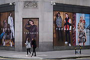 In advance of a re-opening of businesses and before a change to a Tier 2 for London during the second wave of the Coronavirus pandemic, a Londoner walks past posters at the rear of the Topshop clothing retailer which is soon expected to be placed under administration, on 30th November 2020, in London, England. Retailers will once again be open for Christmas business on 3rd December.