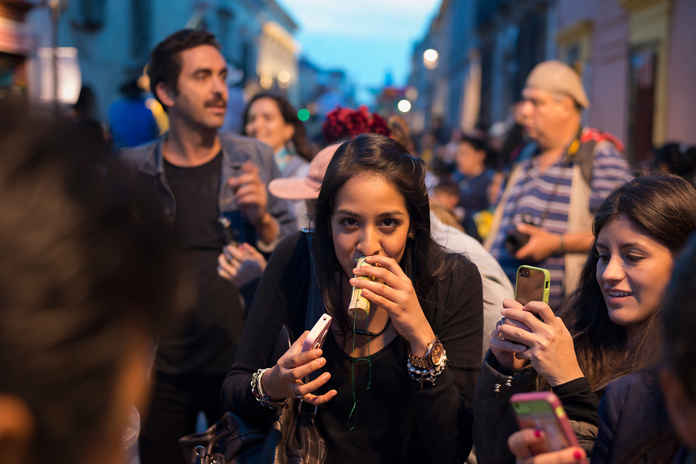 """A young woman takes a sip of an alcohol drink, probably mezcal, that was passed out to people celebrating the Day of the Dead (""""Día de los Muertos"""" in Spanish) in Oaxaca, Mexico."""