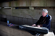 A walk along the River Thames on the Southbank in London. A busker performing under a bridge. This area is very popular especially on the weekends for Londoners to walk and see different arts, culture and entertainment.