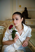 A woman holds a rose in a bedroom of the Ritz Hotel, London