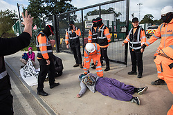 Harefield, UK. 12th September, 2020. Security guards working on behalf of HS2 remove environmental activists acting in solidarity with HS2 Rebellion from the road in front of a gate providing access to a site for the HS2 high-speed rail link. Anti-HS2 activists continue to try to prevent or delay works on the controversial £106bn HS2 high-speed rail link in the Colne Valley where thousands of trees have already been felled.