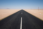 Nominee in 14th (2021) International Colour Awards (Fine Art category)<br /> <br /> One of the most perfect stretches of road that we found in Namibia. Miles of perfect black tarmac with distinctive white markers created such geometry amongst thousands of acres of desert sand. As with most man-made things that I observed in Namibia, they all seemed slightly incongruous within such vast wilderness landscape.