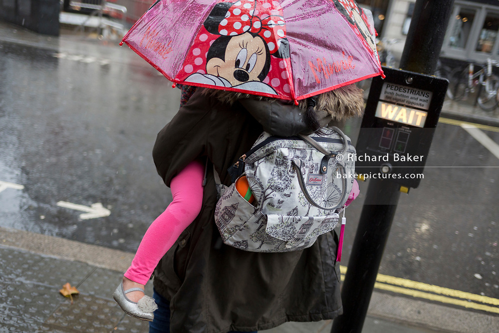 A mother carries her child under a Minnie Mouse umbrella during heavy rainfall on an autumn afternoon near Trafalgar Square, on 24th October 2019, in Westminster, London, England.