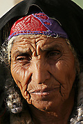 Temam, a 80-yeal-old Bedouin woman, is portrayed in the Bedouin city of Rahat, close to Beer Sheva, the capital of the Negev, a large deserted area in the south of Israel. Numbering around 200.000 in Israel, the Bedouins constitute the native ethnic group of these areas, they farm, grow wheat, olives and live in complete self sufficiency. Many of them were in these lands long before the Israeli State was created and their traditional lifestyle is now threatened by subtle Governmental policies. The seven Bedouin towns already built are all between the 10 more impoverished towns in Israel.