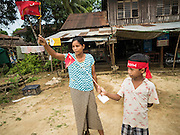 25 OCTOBER 2015 - SHWEPYITHAR, MYANMAR:  People wave National League for Democracy flags while a NLD motorcade passes their home in Shwepyithar, Myanmar. Political parties are in fill campaign mode in Myanmar (Burma). National elections are scheduled for Sunday Nov. 8. The two principal parties are the National League for Democracy (NLD), the party of democracy icon and Nobel Peace Prize winner Aung San Suu Kyi, and the ruling Union Solidarity and Development Party (USDP), led by incumbent President Thein Sein. There are more than 30 parties campaigning for national and local offices.    PHOTO BY JACK KURTZ