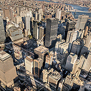 High above lower Manhattan, we have a view of the empty pit where the twin towers stood, and where construction has begun on One World Trade Center.
