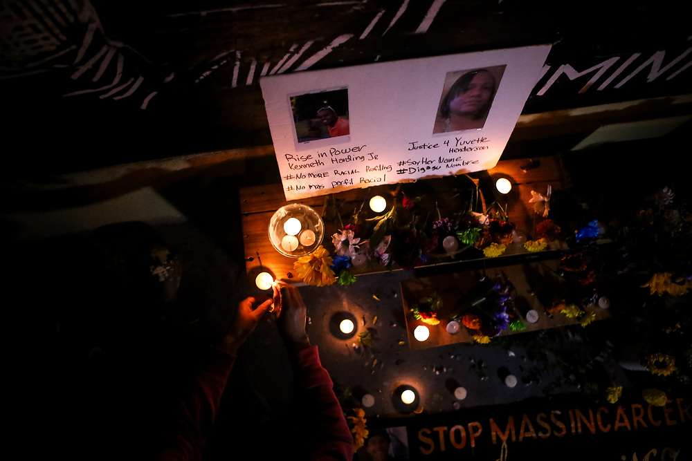 A woman lights a candle at a community altar dedicated to individuals killed by law enforcement on Día de los Muertos outside the Red Poppy Art House in San Francisco, Calif., Monday, November 2, 2015.
