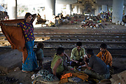 Aarti, a homeless woman who lives with her family by the railway tracks in Okhla, watches as her husband and his friends gamble and play cards. New Delhi, India