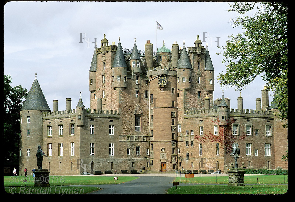 Glamis Castle, childhood home of Queen Mother, framed by statues of James VI and his son Charles I (left, rt);  Glamis, Scotland.
