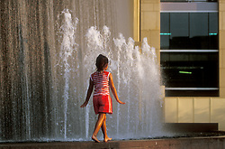 Stock photo of a young girl walking across the base of a fountain