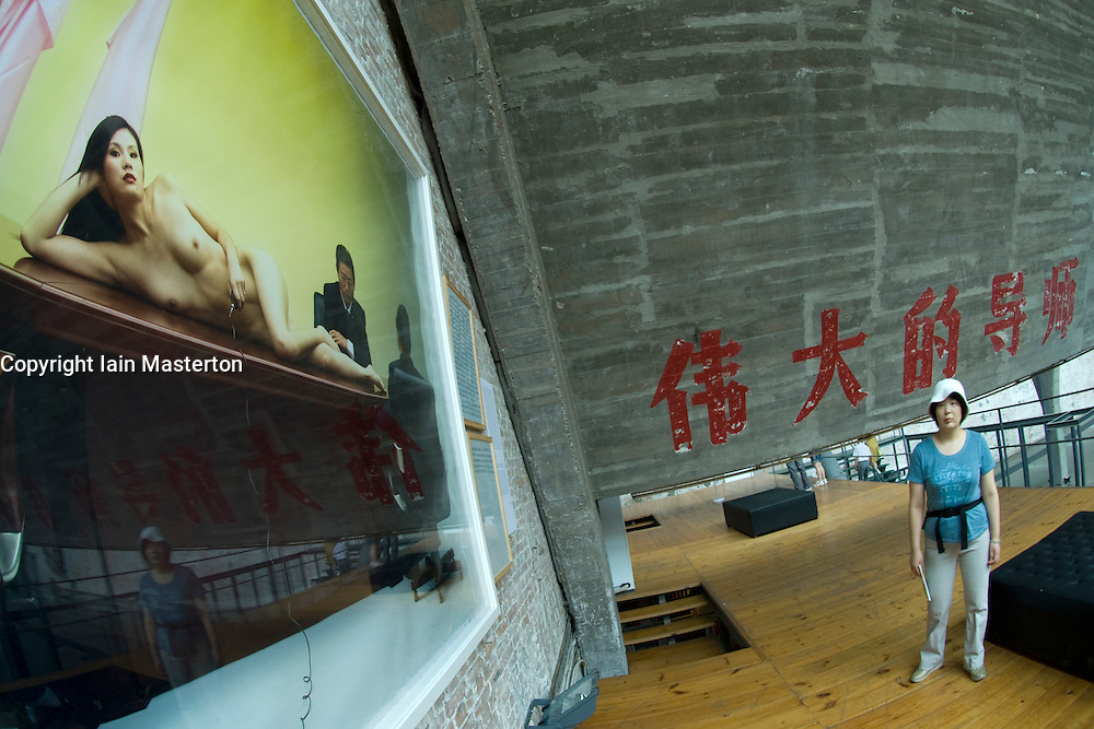 woman looking at nude photographic exhibit in gallery at trendy  798 Art District in Beijing