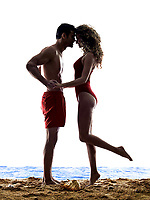 one caucasian couple man and woman lovers kissing on the beach silhouette isolated on white background