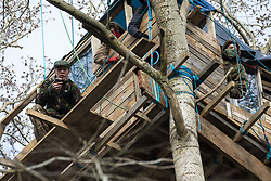 Steeple Claydon, UK. 23 February, 2021. Anti-HS2 activists including Lazer Sandford (l) observe National Eviction Team bailiffs from a tree house during an operation by HS2 Ltd to evict activists living in ancient woodland known as Poors Piece. The activists created the Poors Piece Conservation Project there in spring 2020 after having been invited to stay on the land by its owner, farmer Clive Higgins. Already, local village communities have been hugely impacted by HS2, with 550 acres of land seized including a large section of a nature reserve.