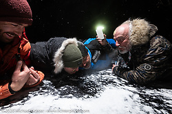 (L>R) Sean Lichter, Simon Pitelet, Frederic Billon and Bertrand Dubet on the frozen lake to make a Baikal Kiss (drill a hole in the ice and fill it with vodka to drink) during the wrap party after the Baikal Mile Ice Speed Festival. Maksimiha, Siberia, Russia. Saturday, February 29, 2020. Photography ©2020 Michael Lichter.