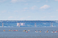 New Windsor, New York - A large group of people in kayaks paddle north on Hudson River as seen from Plum Point on July 31, 2015. The Newburgh-Beacon Bridge is in the background.
