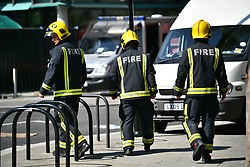 © Licensed to London News Pictures. 17/06/2017. London, UK. Firefighters at the scene of a fire at the Grenfell tower block in west London earlier this week. The blaze engulfed the 27-storey building killing 12 - with 34 people still in hospital, 18 of whom are in critical condition. The fire brigade say that they don't expect to find anyone else alive. Photo credit: Ben Cawthra/LNP