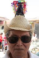 Hombre con sombrero decorado en el desfile de toros del 8 de marzo.