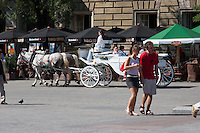 Horse Carriage and people walking on the Rynek in Krakow Poland