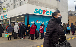 © Licensed to London News Pictures. 13/03/2020. London, UK. A woman wearing a surgical mask walks past Savers in North London as shoppers queue for toilet rolls as panic-buying in supermarkets continues in the UK. Major supermarkets have started to ration certain products after shoppers began to stockpile. 590 cases have been tested positive and ten patients have died from the virus in the UK.. Photo credit: Dinendra Haria/LNP