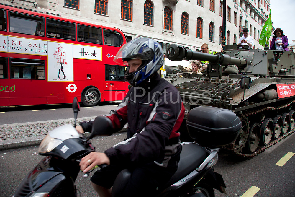 Moped passes the tank while it passes along The Strand. Campaigners and supporters from Oxfam and Amnesty International, as part of the Control Arms coalition, drive an Abbot gun tank around central London to highlight the need for a global Arms Trade Treaty (ATT) to be agreed during a United Nations conference next month (July 2012). London, England, UK. 27th June 2012.