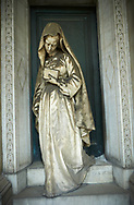 Picture and image of the stone sculpture of a women on the tomb of ship builder Giovanni Battista Piaggio by  Sculptor G. Benetti 1873. Giovanni Battista Piaggio, who is buried here, was a rich ship-owner, whose important role in society is expressed by the professional symbols -the anchor, the ropes, the sand-glass, the globe, the chart that the sculptor Giuseppe Benetti put on the sides of the deceased's bust hosted in the lunette, which surmounts the architecture in Renaissance style of the monument. As a representative of the upper middle class he couldn't die without leaving memories of his social role: Benetti, in order to meet this requirement, represented the widow coming out of the chapel with a prayer-book in her hand. Bringing the mourning in an everyday-life dimension Benetti created a work in accordance with the dictates of the Realism bourgeois. Section A, no 47, The monumental tombs of the Staglieno Monumental Cemetery, Genoa, Italy .<br /> <br /> Visit our ITALY PHOTO COLLECTION for more   photos of Italy to download or buy as prints https://funkystock.photoshelter.com/gallery-collection/2b-Pictures-Images-of-Italy-Photos-of-Italian-Historic-Landmark-Sites/C0000qxA2zGFjd_k<br /> If you prefer to buy from our ALAMY PHOTO LIBRARY  Collection visit : https://www.alamy.com/portfolio/paul-williams-funkystock/camposanto-di-staglieno-cemetery-genoa.html