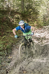 Mountain biker riding through puddle and splashing water in forest
