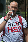 Matt Bishop from the Stop HS2 camp in Cubbington Wood addresses activists from HS2 Rebellion, an umbrella campaign group comprising longstanding campaigners against the HS2 high-speed rail link as well as Extinction Rebellion activists, at a protest outside the Department for Transport on 4 September 2020 in London, United Kingdom. Activists glued themselves to the doors and pavement outside the building and sprayed fake blood around the entrance during a protest which coincided with an announcement by HS2 Ltd that construction of the controversial £106bn high-speed rail link will now commence.