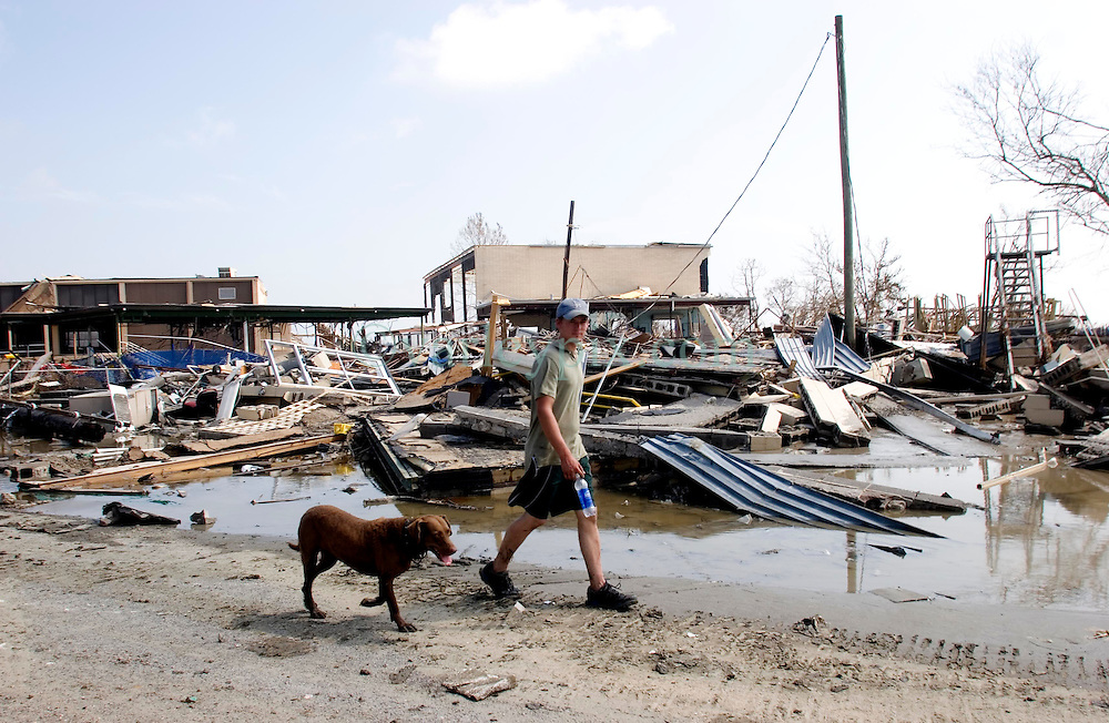 26th Sept, 2005.  Cameron, Louisiana. Hurricane Rita aftermath.<br /> The destroyed remains of a downtown business in Cameron, Louisiana two days after the storm ravaged the small town. local man Aaron Stokes from nearby Carlyss surveys the damage with his dog Maggie.<br /> Photo; ©Charlie Varley/varleypix.com