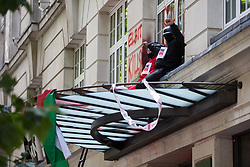 London, UK. 6th August, 2021. Pro-Palestinian activists from Palestine Action occupy an area above the entrance to the headquarters of Elbit Systems UK after daubing it with painted messages. The activists were protesting against the presence in the UK of Elbit Systems, an Israel-based company developing technologies for military applications including drones, precision guidance, surveillance and intruder-detection systems used against the Palestinians, and their action formed part of a concerted campaign by Palestine Action against the Israeli arms company.