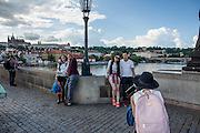 Different ages and nationalities are documenting their visit in Prague on Charles Bridge with smart phones and cameras. The Charles Bridge (Czech: Karlův most) is a famous historic bridge that crosses the Vltava river in Prague, Czech Republic and is probably the Nr.1 tourists magnet in the city.