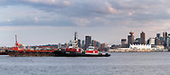 Seaspan Raven and Seaspan Hawk Tug Boats manourvre a barge in Burrard Inlet. Photographed from the Kings Mill Walk Dog Park (Spirit Trail) in North Vancouver. Buildings in the background are in downtown Vancouver and include Harbour Center, Pan Pacific Hotel and Canada Place.