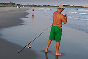 A man baits his hook while fishing at sunset on the town beach, Narragansett, Rhode Island.