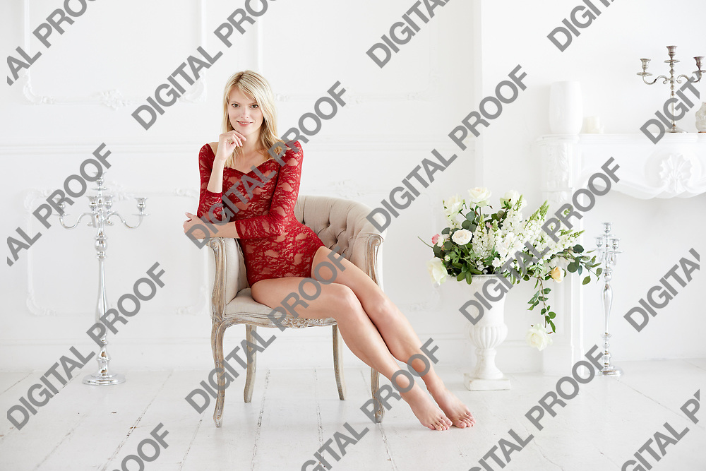Happy caucasian woman in a red lace bodysuit and barefoot sitted in a chair with frontal look in a white interior room.  Women boudoir concept.