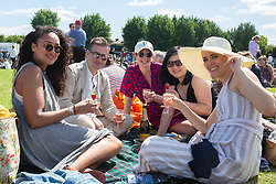 Friends enjoy strawberries and Prosecco as they wait in the queue during day one of the Wimbledon Championships at the All England Lawn Tennis and Croquet Club, Wimbledon. Photo credit should read: Katie Collins/EMPICS