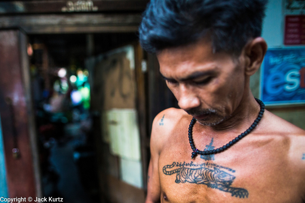 """13 JANUARY 2013 - BANGKOK, THAILAND:  A man with a """"sak yant"""" or holy tiger tatoo on his chest in front of his home in the Bang Luang neighborhood of Bangkok. He believes the tattoo enables him to channel the power of the tiger. The Bang Luang neighborhood lines Khlong (Canal) Bang Luang in the Thonburi section of Bangkok on the west side of Chao Phraya River. It was established in the late 18th Century by King Taksin the Great after the Burmese sacked the Siamese capital of Ayutthaya. The neighborhood, like most of Thonburi, is relatively undeveloped and still criss crossed by the canals which once made Bangkok famous. It's now a popular day trip from central Bangkok and offers a glimpse into what the city used to be like.     PHOTO BY JACK KURTZ"""