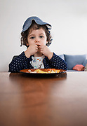 Young toddler siting at a table eating with her hands