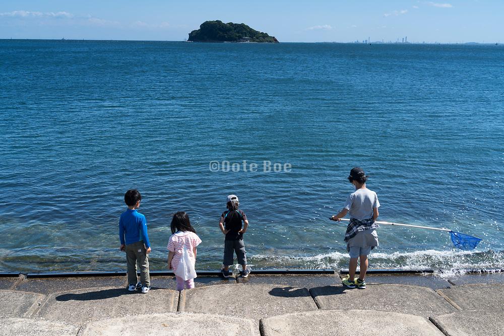 little children watching for fish Tokyo Bay Yokosuka Japan
