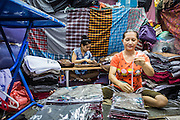 06 JUNE 2013 - BANGKOK, THAILAND:   A woman and her assistant package clothes made in Thailand for export in Bobae Market in Bangkok. She said the clothes were going to Uganda. Bobae Market is a 30 year old market famous for fashion wholesale and is now very popular with exporters from around the world. Bobae Tower is next to the market and  advertises itself as having 1,300 stalls under one roof and claims to be the largest garment wholesale center in Thailand.       PHOTO BY JACK KURTZ