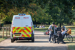 © Licensed to London News Pictures. 19/09/2020. London, UK. Walkers enjoy a stroll in the warm sunshine as Police patrol Hyde Park in London on the first weekend of the Rule of Six where gatherings of over six people have now been banned by the Government after a spike in coronavirus cases. Prime Minister Boris Johnson announced yesterday that the UK was heading for a second wave with the North East already under lockdown.  Photo credit: Alex Lentati/LNP