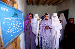 YAFTAL PAYAN, 31 July 2005..Women standing at the entrance of Bitha Bala's Vocational Training Centre.....The VTC aim is to make women aware of their onwn status as Mother and as Woman, by giving lessons on maternity, reproductive health, family planning and post-natal issues.....According to United Nations Population Fund, Afghanistan has among the world?s highest rates of maternal mortality, and Badakhshan has the highest rates ever recorded anywhere in the world, with one mother dying in every 15 births. Underage marriage is one of the primary causes of maternal mortality.....The VTC is funded by UNFPA and implemented by IBNSINA.