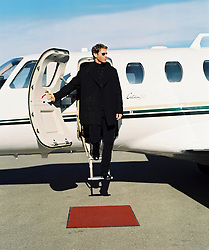 Good looking well-dressed man in sunglasses getting off his lear jet