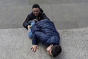 A man helps a young boy up on to the plinth below Nelson's Column, on 1st May, in Trafalgar Square, London, England.