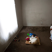 Apartment complex where migrant workers live is dilapadated and infested. This family can't sleep in this room because of the extensive water damage and rot. Several of the girls toys lay on the cardboard. Please contact Todd Bigelow directly with your licensing requests.