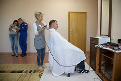 Expedition 57 Flight Engineer Nick Hague of NASA gets his hair cut as Expedition 57 backup crewmember David Saint-Jacques of the Canadian Space Agency waits his turn, Tuesday, Oct. 9, 2018 at the Cosmonaut Hotel in Baikonur, Kazakhstan. Hague and Expedition 57 Flight Engineer Alexey Ovchinin of Roscosmos are scheduled to launch onboard a Soyuz rocket October 11 and will spend the next six months living and working aboard the International Space Station. Photo Credit: (NASA/Bill Ingalls)